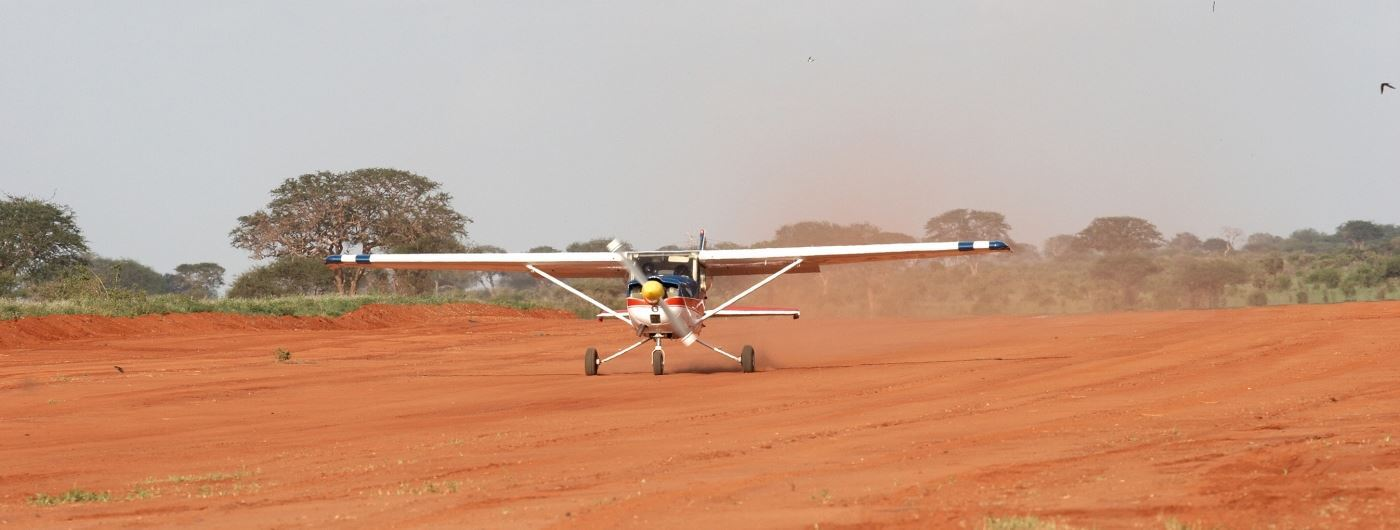 Light aircraft taking off from Kenyan bush airstrip