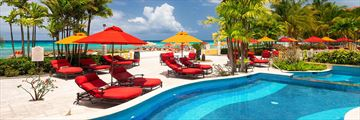 Beachfront pool with red sun loungers and yellow and red umbrellas