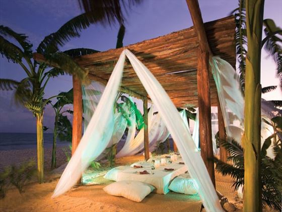 White drapery, low table and pillow seating on the beach make for an elegant setting for a wedding or group dinner.