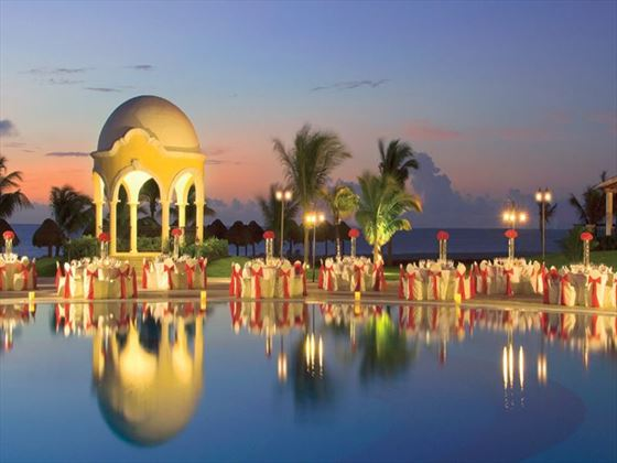 Lights reflect off the water at wedding or party setup around the pool at night, with the wedding gazebo in the distance