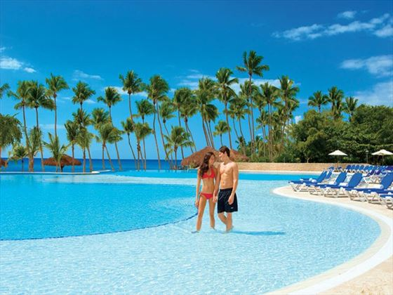A couple wades in the expansive infinity pool at Dreams La Romana