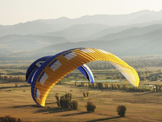 Paragliders soaring above the misty hills of Jackson, Wyoming