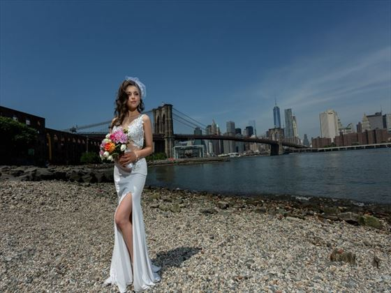 Happy bride on Pebble Beach with New York skyline