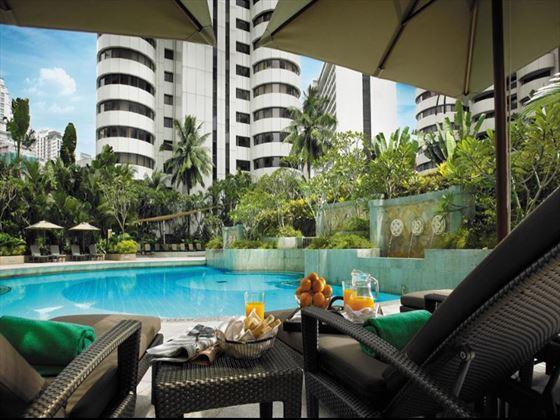 Swimming pool and sun loungers at Shangri-La Kuala Lumpur