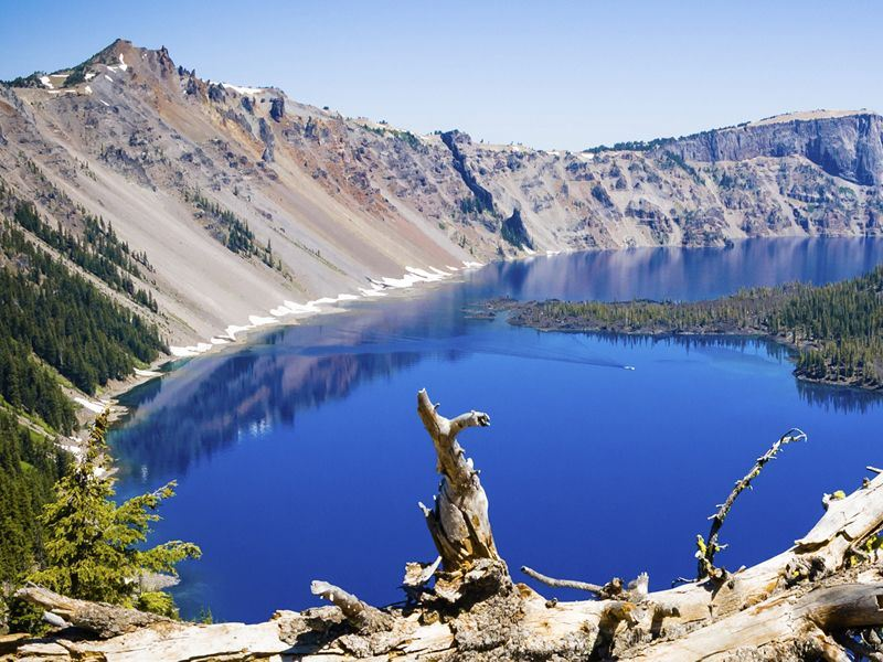 Small boat on calm sapphire waters of Crater Lake
